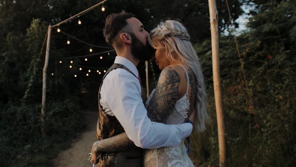 groom kisses brides forehead at wilderness wedding venue in kent