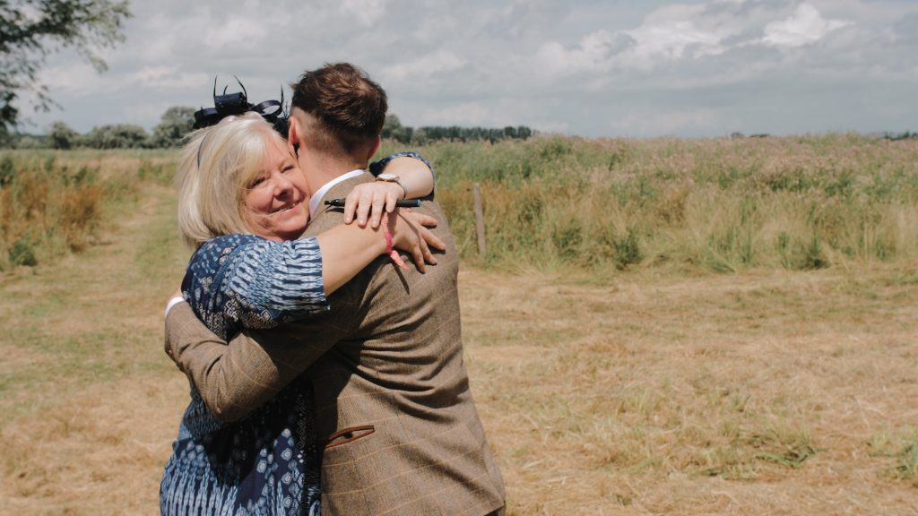 Groom and guest hug at wilderness wedding venue in Kent