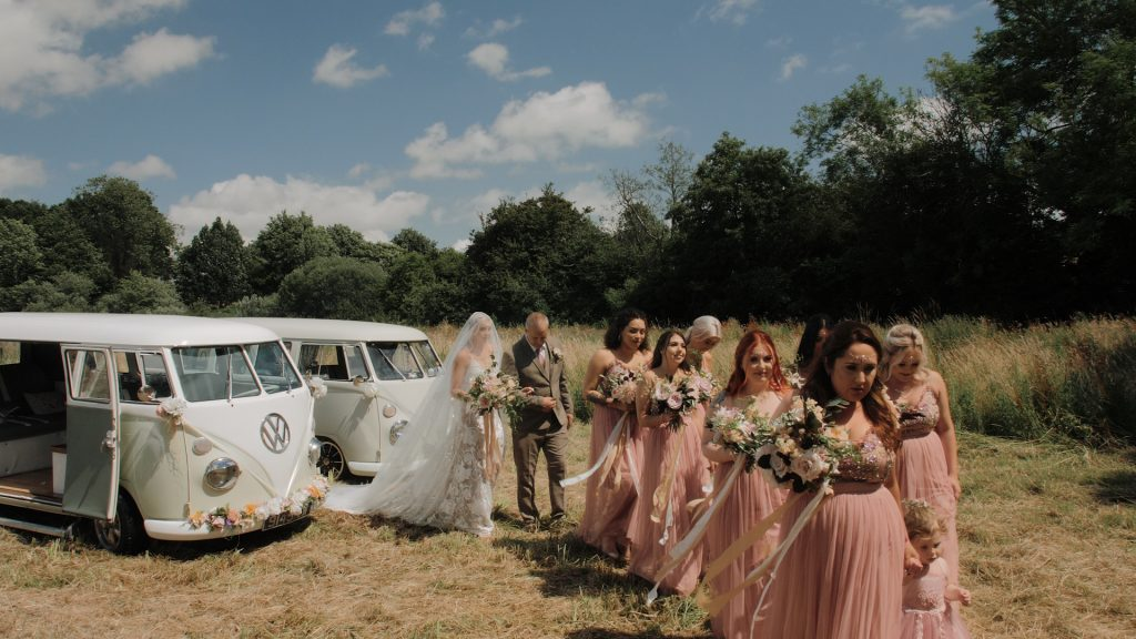 bridesmaids walk down the aisle at wilderness wedding venue in Kent