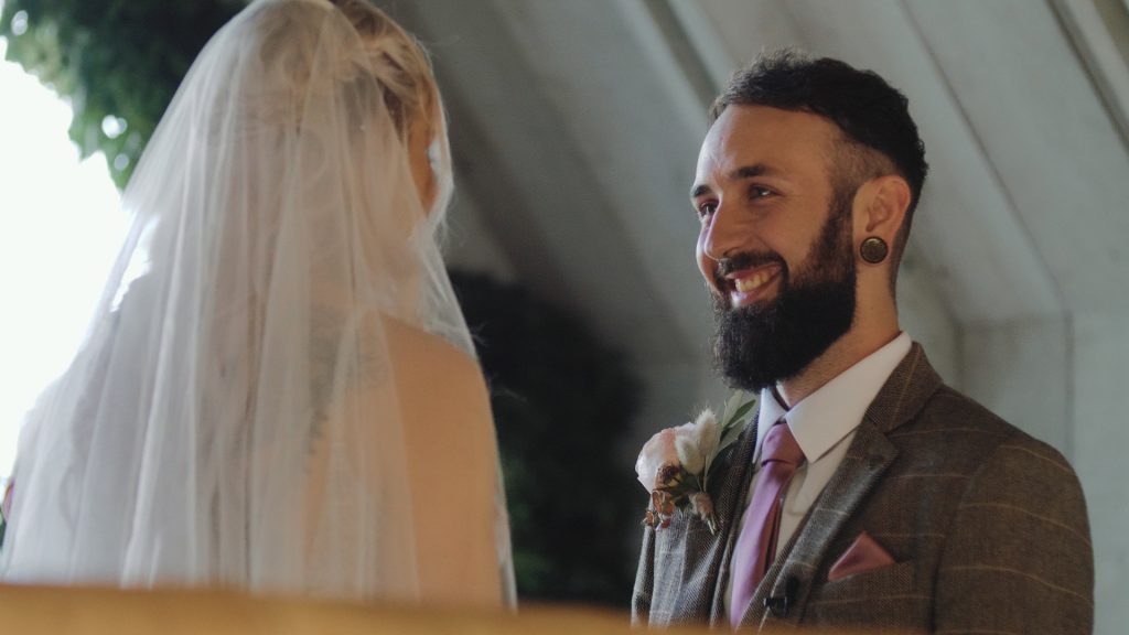 groom smiles during vows at wilderness wedding venue in Kent