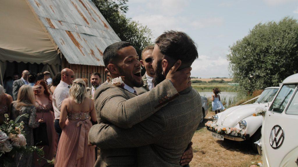 groomsman congratulates groom at wilderness wedding venue in Kent