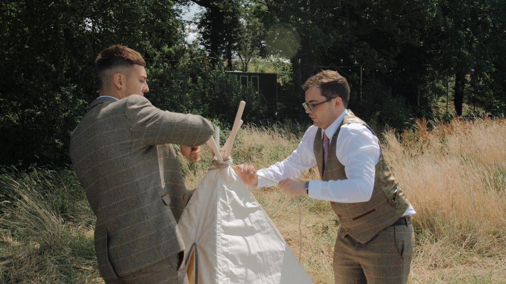 groomsmen erect tipi at wilderness wedding venue kent