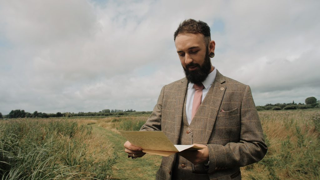 Groom reads letter from bride at wilderness weddings in kent