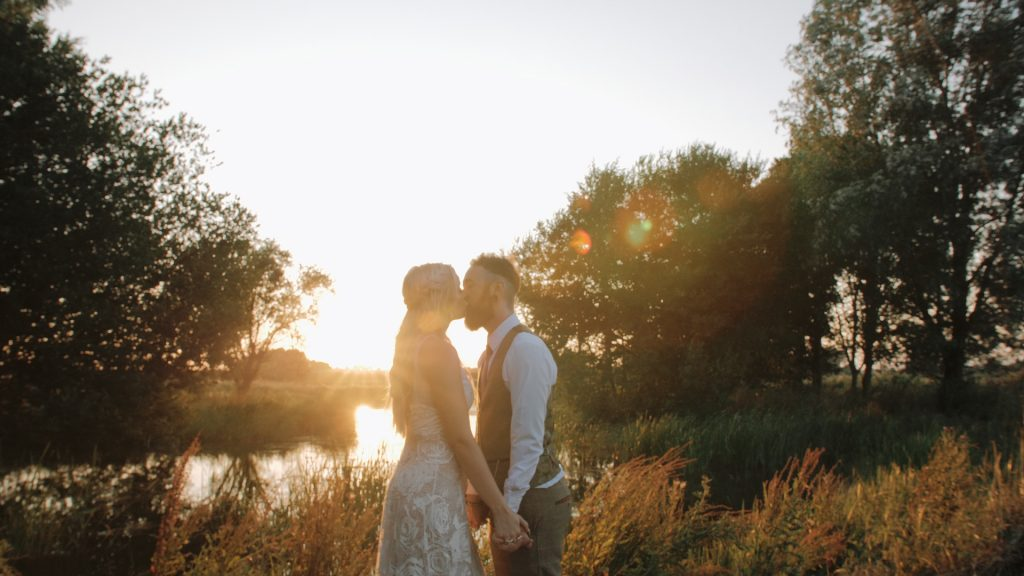 bride and groom kiss in the sunset at wilderness weddings