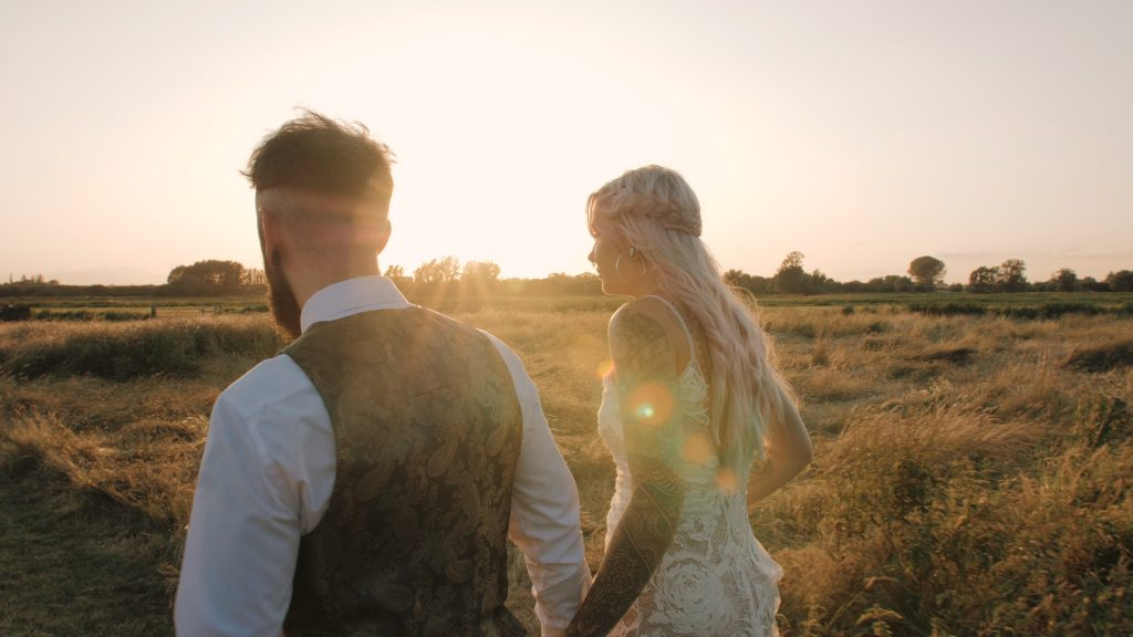 shot from behind bride and groom walking in the meadow at wilderness wedding venue in Kent