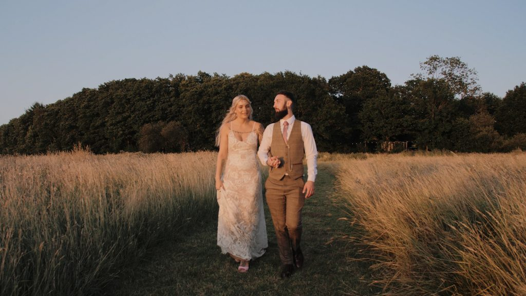 bride and groom walk in the meadow at wilderness wedding venue in kent